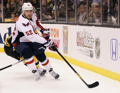 BOSTON, MA - APRIL 12:  Mike Green #52 of the Washington Capitals takes the puck in the first period against the Boston Bruins in Game One of the Eastern Conference Quarterfinals during the 2012 NHL Stanley Cup Playoffs at TD Garden on April 12, 2012 in Boston, Massachusetts.  (Photo by Elsa/Getty Images)