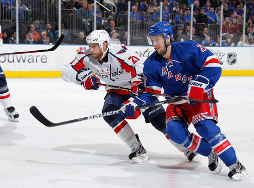 NEW YORK, NY - APRIL 28: Derek Stepan #21 of the New York Rangers skates against Brooks Laich #21 of the Washington Capitals in Game One of the Eastern Conference Semifinals during the 2012 NHL Stanley Cup Playoffs at Madison Square Garden on April 28, 2012 in New York City. (Photo by Scott Levy/NHLI via Getty Images)